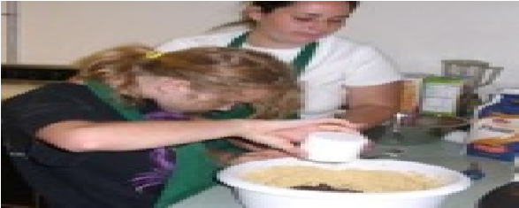 Photo of female student baking with instructor.