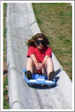 Photo of a female student riding an alpine slide.